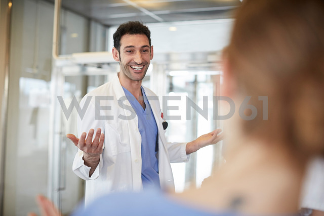 Cheerful young male doctor gesturing to female nurse while standing in lobby at hospital - MASF09262