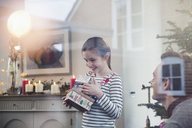 Eager girl gathering Christmas gifts - HOXF03771
