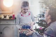 Daughter giving stack of Christmas gifts to father in living room - HOXF03777