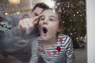 Playful father and daughter drawing in condensation on wet winter window - HOXF03789