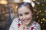 Portrait smiling, confident girl in Christmas living room - HOXF03792