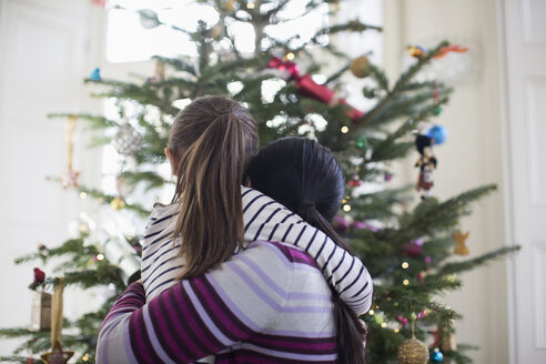 Affectionate mother and daughter hugging in front of Christmas tree - HOXF03813