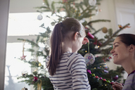 Mother and daughter decorating Christmas tree - HOXF03822