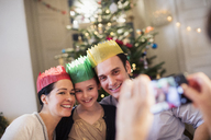 Happy family in paper crowns posing for photograph in Christmas living room - HOXF03825