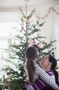Affectionate mother and daughter looking up at Christmas tree - HOXF03846