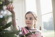 Curious girl touching ornament on Christmas tree - HOXF03849