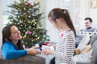 Family opening Christmas gifts in living room - HOXF03855
