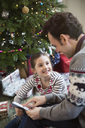 Father reading book with daughter at Christmas tree - HOXF03861