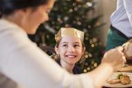 Smiling girl in paper crown enjoying Christmas dinner - HOXF03882
