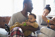 Happy multi-ethnic family in pajamas cuddling on sofa - HOXF03912