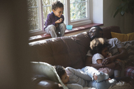 Happy father and children cuddling on living room sofa - HOXF03918