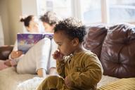 Innocent baby boy sucking thumb on sofa - HOXF03924