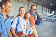 Happy friends walking in airplane hangar - CAIF21743