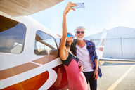 Couple taking selfie with camera phone at small airplane - CAIF21746