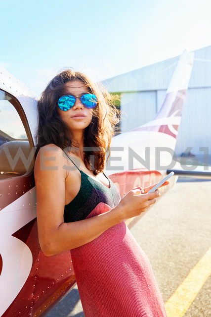 Portrait confident young woman with smart phone leaning against small airplane - CAIF21752