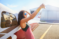 Confident young woman taking selfie with camera phone at small airplane on sunny tarmac - CAIF21758