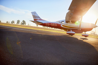 Propellor airplane landing on sunny tarmac - CAIF21764