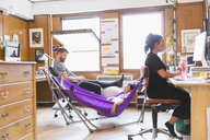 Creative designers relaxing in hammock in office - CAIF21776