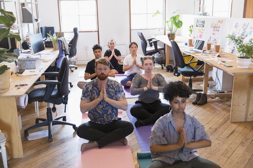 Creative business people meditating in office - CAIF21827