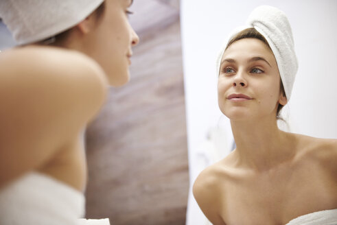 Mirror image of young woman examining her face in the bathroom - ABIF00983