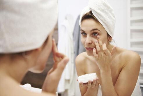 Mirror image of young woman applying moisturizer in bathroom - ABIF00986