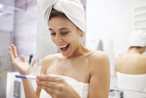 Portrait of excited young woman looking at pregnancy test in bathroom - ABIF00995