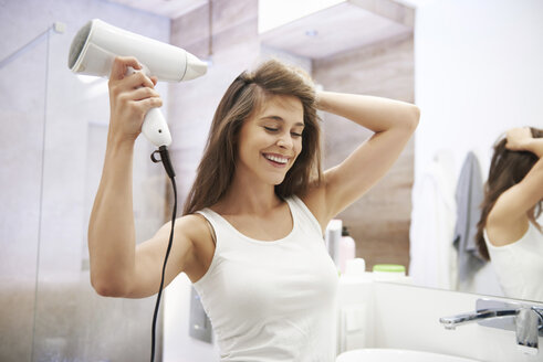 Portrait of laughing woman using hair dryer in the bathroom - ABIF01001