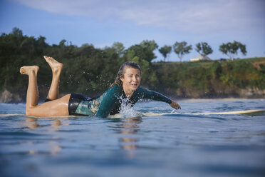 Indonesia, Bali, Balangan beach, female surfer lying on surfboard - KNTF01367