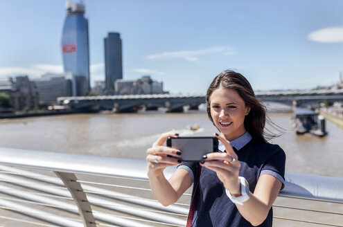 UK, London, woman taking a selfie on the Millennium Bridge - MGOF03781