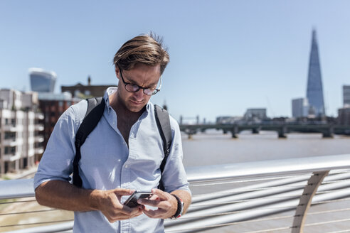 UK, London, man using his smartphone on the Millennium Bridge - MGOF03784