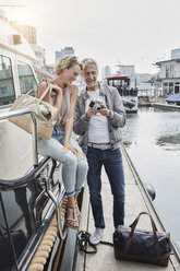 Older man with camera and young woman standing with travelling bags on jetty next to yacht - RORF01552