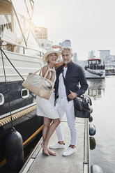 Older man and young woman standing with travelling bags on jetty next to yacht - RORF01555