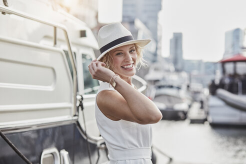 Portrait of happy young woman wearing a hat at a marina next to a yacht - RORF01558