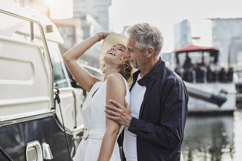Older man and young woman at a marina next to a yacht - RORF01561