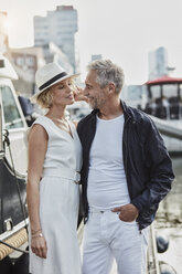 Older man and young woman at a marina next to a yacht - RORF01564