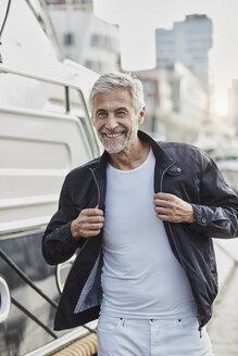 Smiling mature man at a marina next to a yacht - RORF01567