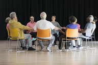 Active seniors meditating, holding hands in circle - CAIF21868