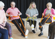Active seniors exercising in circle, using straps to stretch legs - CAIF21871