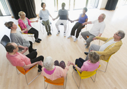 Active seniors holding hands in circle, meditating in community center - CAIF21886