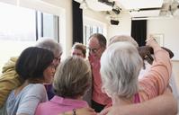 Active seniors hugging in circle huddle - CAIF21901