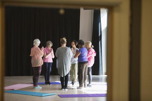 Serene active seniors practicing yoga in circle - CAIF21907
