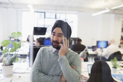 Serious Indian businessman in turban talking on smart phone in office - CAIF21916