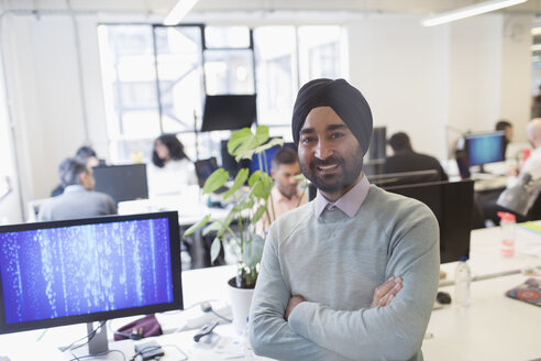 Portrait smiling, confident Indian computer programmer in turban in office - CAIF21934