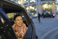 Smiling businesswoman talking on smart phone in crowdsourced taxi at night - CAIF21949