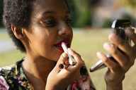 Portrait of young woman applying lipstick outdoors - GIOF04299