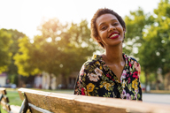 Portrait of smiling young woman on bench in a park - GIOF04305