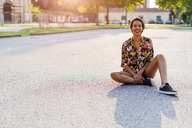 Portrait of laughing young woman sitting outdoors at sunset - GIOF04308