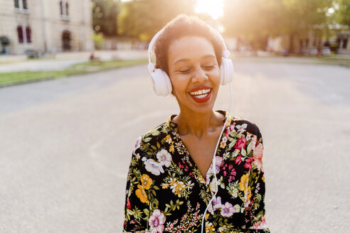 Happy fashionable young woman with headphones outdoors at sunset - GIOF04320