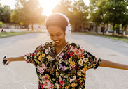 Happy fashionable young woman with headphones dancing outdoors at sunset - GIOF04323