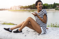 Happy young woman sitting on wall at the riverside holding cell phone - GIOF04326